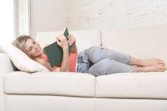 Giovane bello libro di lettura caucasico della donna che studia menzogne comoda sul sofà domestico che sembra felice fotografia stock