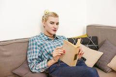 giovane bello libro di lettura della ragazza che si siede sul sofà nella stanza Fotografie Stock
