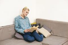 giovane bello libro di lettura della ragazza che si siede sul sofà nella stanza Immagini Stock Libere da Diritti