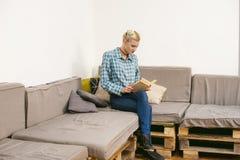 giovane bello libro di lettura della ragazza che si siede sul sofà nella stanza Fotografia Stock