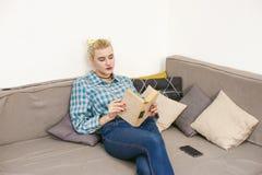 giovane bello libro di lettura della ragazza che si siede sul sofà nella stanza Immagine Stock
