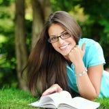 Giovane bello libro di lettura della ragazza in un parco di verde di estate fotografia stock libera da diritti