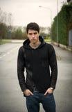 Giovane bello in maglione nero di maglia con cappuccio all'aperto in via fotografie stock