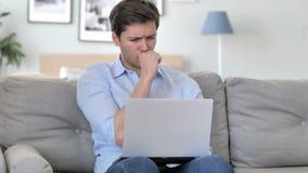 Giovane bello malato che tossisce mentre lavorando al computer portatile all'ufficio creativo archivi video