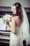 Giovane bello mazzo della tenuta della sposa dei fiori. Immagini Stock Libere da Diritti