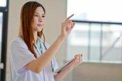 Giovane bello medico femminile sorridente felice che mostra area in bianco f Fotografia Stock