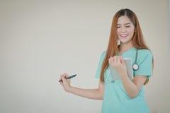 Giovane bello medico femminile sorridente felice che mostra area in bianco f Immagini Stock Libere da Diritti