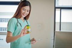 Giovane bello medico femminile sorridente felice che mostra area in bianco f Fotografie Stock Libere da Diritti