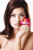 Giovane bello modello asiatico con l'orchidea viola fotografia stock libera da diritti
