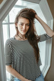 giovane bello modello della donna con capelli lunghi sudici in blue jeans strappate e nella seduta a strisce della maglietta dell Immagine Stock