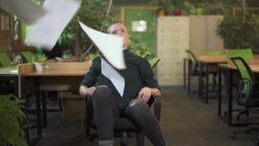 Giovane bello nella sedia verde moderna di guida dell'ufficio di eco e carte di lancio con il fronte serio Movimento lento video d archivio