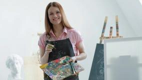 Giovane bello pittore della donna fra i cavalletti e le tele in uno studio luminoso stock footage