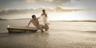 Giovane bello pomeriggio di spesa delle coppie sulla spiaggia con la vecchia vasca da bagno immagine stock libera da diritti