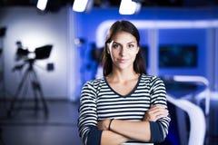 Giovane bello presentatore di televisione castana allo studio che sta accanto alla macchina fotografica Direttore della TV al red Immagini Stock