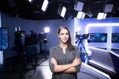 Giovane bello presentatore di televisione castana allo studio che sta accanto alla macchina fotografica Direttore della TV al red Immagini Stock Libere da Diritti