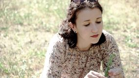 Giovane bello ritratto castana della ragazza che si siede sul fiore della tenuta dell'erba stock footage