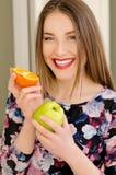 Giovane bello ritratto del primo piano della ragazza con frutta arancio, rossetto rosso e trucco perfetto Fotografia Stock Libera da Diritti