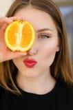 Giovane bello ritratto del primo piano della ragazza con frutta arancio, rossetto rosso e trucco perfetto Immagini Stock Libere da Diritti