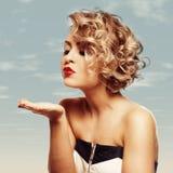 Giovane bello salto femminile biondo baciato al suo biglietto di S Immagine Stock