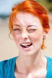 Giovane bello sbattere le palpebre della donna della testarossa Fotografia Stock