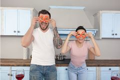 Giovane bello sciocco delle coppie nella cucina Tengono i pezzi di pepe bulgaro intorno ai loro occhi e risata immagini stock libere da diritti