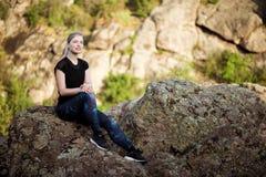 Giovane bello sorridere allegro della ragazza, sedentesi sulla roccia in canyon Fotografie Stock