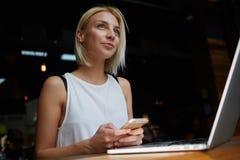 Giovane bello telefono cellulare femminile biondo della tenuta mentre sedendosi con il NET-libro portatile nell'interno della caf Fotografia Stock