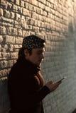 Giovane bello in un berretto da baseball con uno smartphone online immagine stock libera da diritti