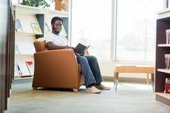 Giovane biblioteca di Reading Book In dello studente Immagine Stock Libera da Diritti