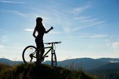 Giovane bicicletta felice di guida della donna nelle montagne al giorno di estate fotografia stock libera da diritti