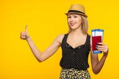 Giovane biglietto emozionante sorridente del passaggio di imbarco del passaporto della tenuta della studentessa isolato su fondo  fotografie stock libere da diritti