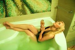 Giovane bionda attraente nel bagno con vetro di champagne Fotografia Stock