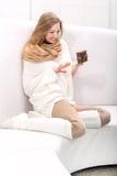 Giovane bionda dai capelli lunghi che si siede su un sofà con un presente Immagini Stock Libere da Diritti
