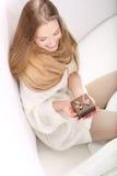 Giovane bionda dai capelli lunghi che si siede su un sofà con una casella attuale Fotografie Stock Libere da Diritti