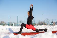 Giovane bionda femminile caucasica in ghette viola che allungano esercizio su una pista corrente rossa in uno stadio nevoso misur immagini stock