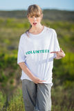 Giovane bionda naturale che indica alla sua maglietta d'offerta Fotografia Stock
