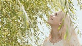 Giovane bionda russa della ragazza che posa contro un fondo dei rami di albero del salice video d archivio