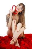 Giovane biondo con un cuore rosso del knit fotografia stock