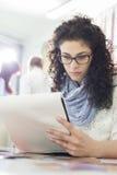 Giovane blocco note della lettura della donna di affari all'ufficio creativo con i colleghi nel fondo immagini stock