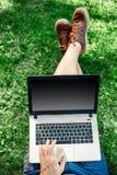 Giovane blogger che si siede sull'erba e che lavora con il computer portatile Immagine Stock Libera da Diritti