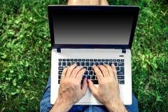 Giovane blogger che si siede sull'erba e che lavora con il computer portatile Immagini Stock Libere da Diritti