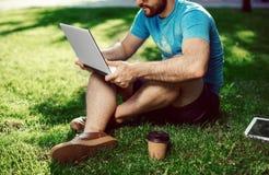 Giovane blogger che si siede sull'erba e che lavora con il computer portatile Fotografia Stock