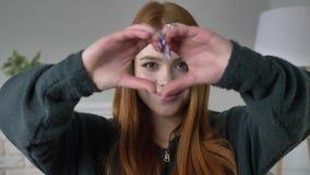 Giovane blogger dai capelli rossi della ragazza, ritratto, esaminando macchina fotografica, sorridere, mostrante segno di cuore,  stock footage