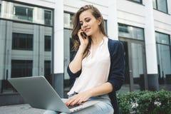 Giovane blogger femminile che lavora al computer portatile moderno sopra all'aperto nel parco urbano Immagine Stock
