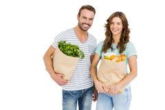 Giovane borsa felice della tenuta delle coppie delle verdure immagini stock