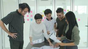 Giovane 'brainstorming' del gruppo di affari che divide le nuove idee in ufficio moderno video d archivio