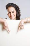 Giovane brunette attraente che tiene tabellone per le affissioni in bianco. Immagine Stock