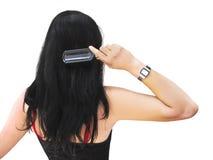 Giovane brunette che spazzola i suoi capelli Fotografie Stock Libere da Diritti