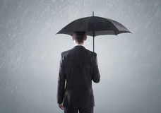 Giovane busienssman astuto che sta nella pioggia Immagine Stock