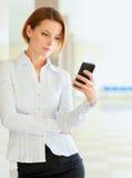 Giovane busineswoman che sta con il telefono in ufficio fotografie stock libere da diritti